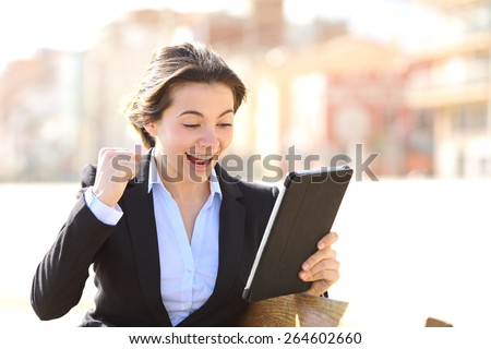 Euphoric successful executive watching a tablet sitting in a bench in a park - stock photo