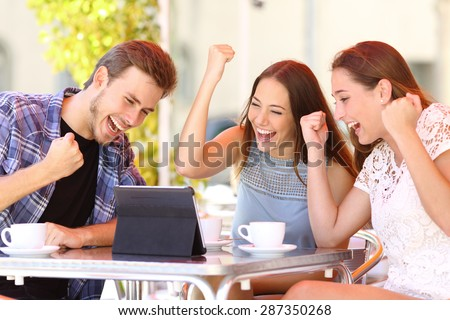 Euphoric winner friends using a tablet in a coffee shop terrace - stock photo