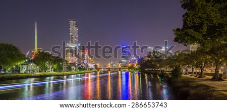 Eureka tower and Art centre with light trail from boat across Yarra river at night, Melbourne City Australia