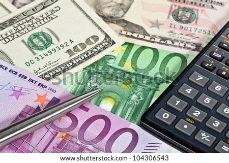 Euro and dollar banknotes, calculator and a pen