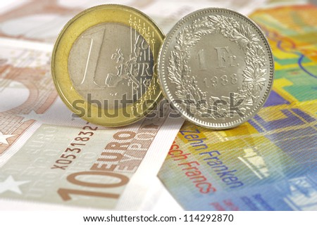 euro and swiss franc coin on banknotes - stock photo