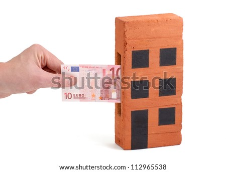 Euro bank note being inserted to or drawn from a block of flats - stock photo