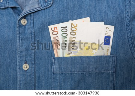 euro bank note in jeans shirt pocket - stock photo