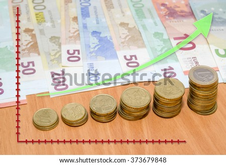 euro banknote with arrow on wooden table - stock photo