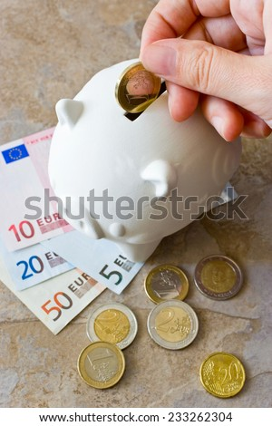 Euro banknotes and coins with piggy bank - hand inserting coin - stock photo