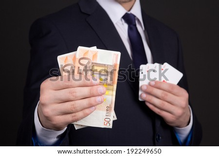 euro banknotes and four aces cards in mans hands