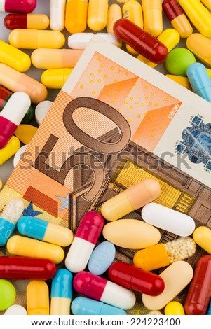 euro banknotes and tablets, symbol photo for costs of medications and health insurance. - stock photo