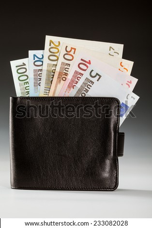 Euro banknotes in leather wallet on dark background - stock photo