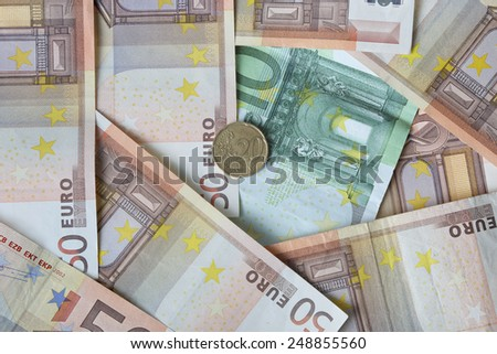 Euro banknotes of fifty and one hundred denomination with twenty cents coin lies over them - money concept and financial background - stock photo