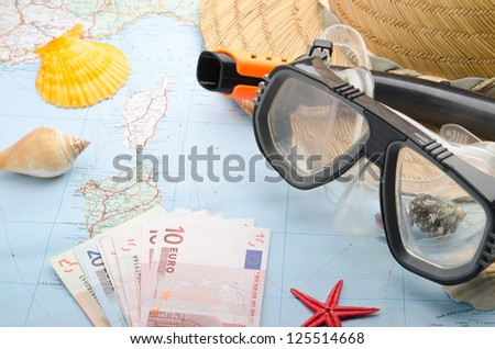 Euro banknotes on a map with snorkel mask - stock photo