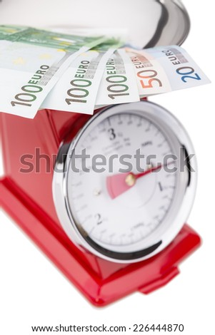 Euro banknotes on the scales. Euro currency in inflation. - stock photo