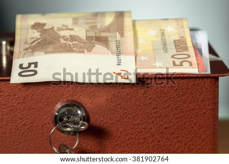 Euro banknotes over a metal moneybox - stock photo
