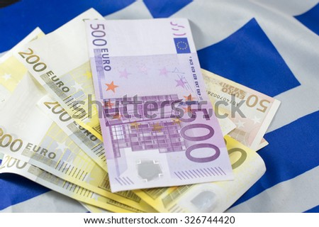 Euro banknotes stacked on the Greek flag
