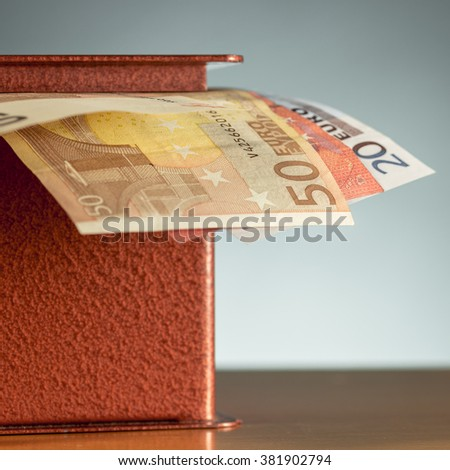 Euro banknotes sticking out of a metal moneybox - stock photo