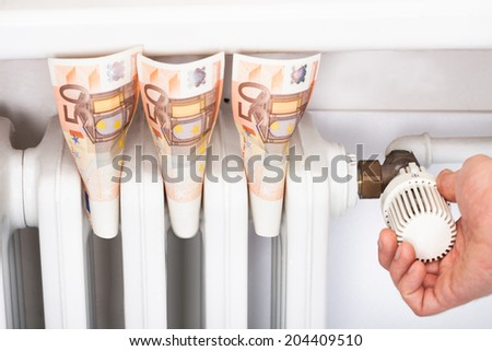 Euro banknotes stuck in radiator with man adjusting thermostat - stock photo