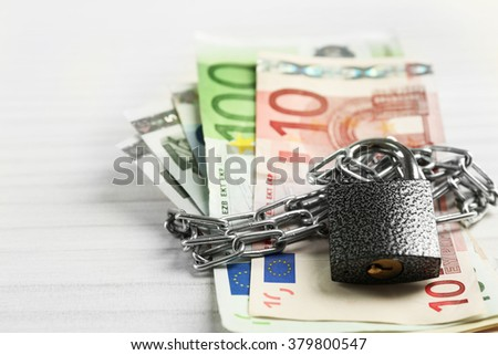 Euro banknotes with lock and chain on wooden table background
