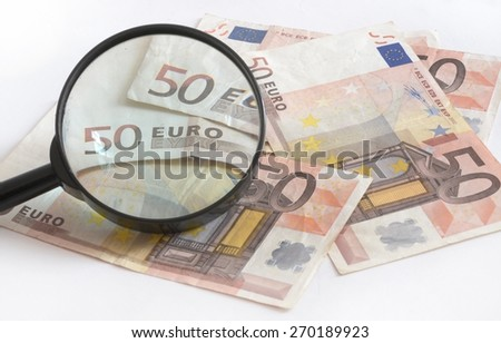 Euro banknotes with magnifying glass