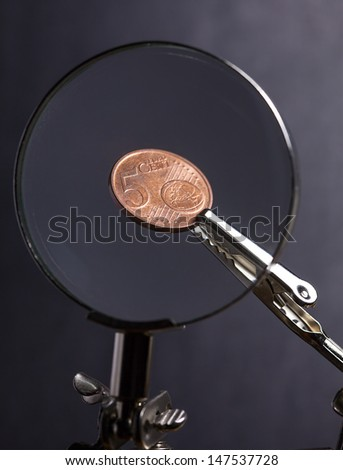 Euro cent in clip over magnifier lens. Finance concept. - stock photo