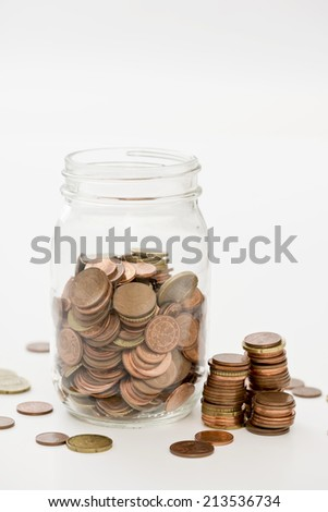 euro cents collected in a glass jar on white background