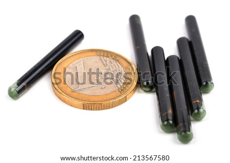 euro coin and animal id implants on a white background - stock photo