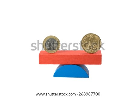 Euro coin and the US one dollar coin stand on the swing from wooden color blocks. Swing coin is in equilibrium - stock photo