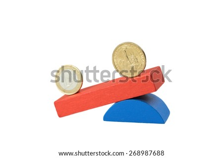 Euro coin and the US one dollar coin stand on the swing from wooden color blocks. Swing is on the side with the US dollar amount. Side view. - stock photo