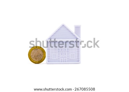 euro coin next to the house on a white background - stock photo