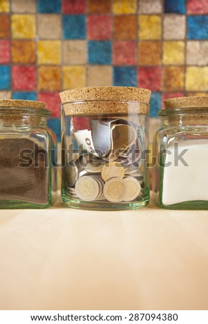Euro coins and banknotes into crystal jar closed with cork plugs between coffee and white sugar on orange background - stock photo