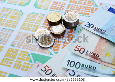 Euro coins and banknotes on map background - stock photo