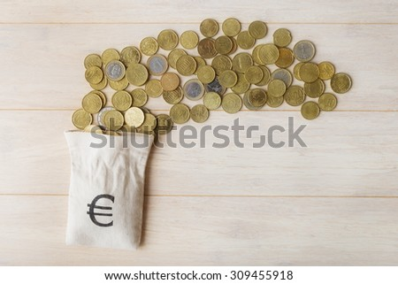 Euro coins and empty money bag over wooden background - stock photo