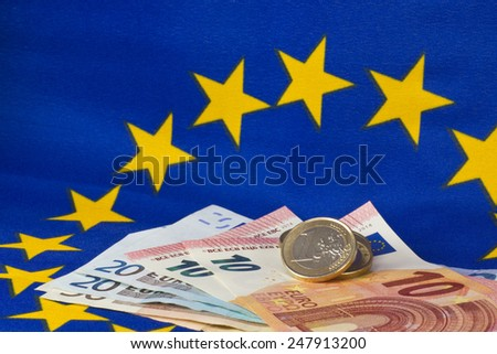 Euro coins and notes in front of EU flag - stock photo