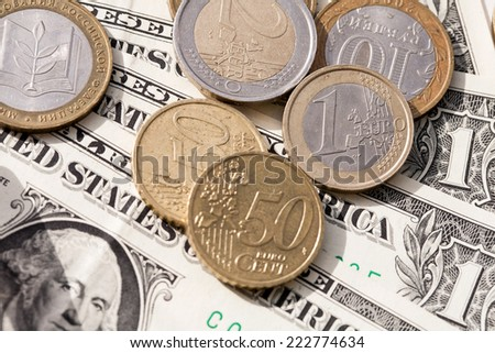 Euro coins and the ruble against the backdrop of the American dollar - stock photo