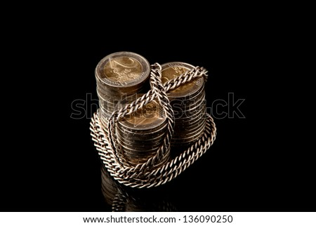 EURO coins chained with silver chain on black background. Studio shot.