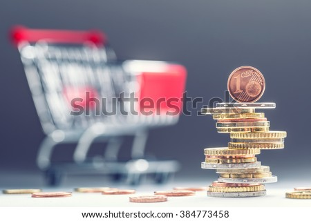 Euro coins. Euro money. Euro currency.Coins stacked on each other in different positions. Money concept. Shopping trolley. Shopping cart in the background. - stock photo