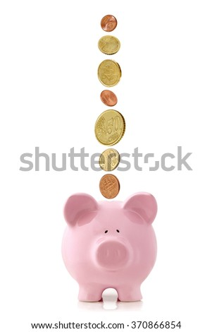 Euro coins falling into a pink piggy bank, isolated on white. - stock photo