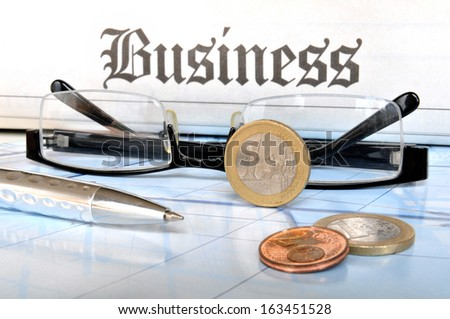 Euro coins, glasses and ball pen in front of the lettering business - stock photo