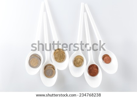 euro coins in teaspoons - stock photo