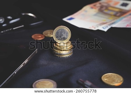 euro coins on a black background surrounded by content of the pockets - stock photo