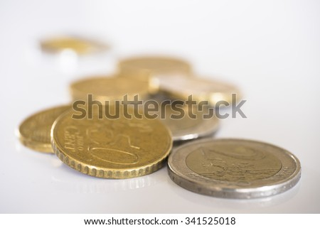 Euro coins on a white background with shallow depth of field - stock photo