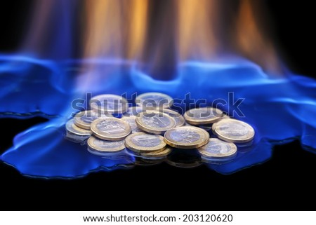euro coins on fire on black background - stock photo