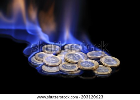 euro coins on fire on black background