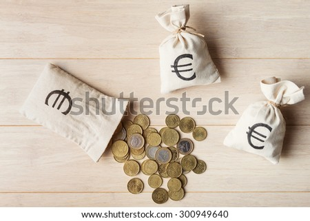 Euro coins with money bags on wooden background, top view