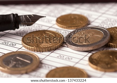 Euro coins with pen and financial chart