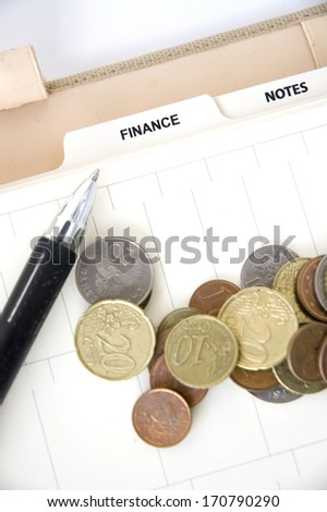 euro coins with pen on finance page of planner