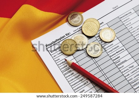 Euro coins with pencil and document on german flag - stock photo