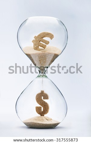 Euro-dollar exchange rate. Dollar sign made out of falling sand from euro sign flowing through hourglass