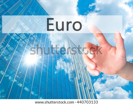 Euro - Hand pressing a button on blurred background concept . Business, technology, internet concept. Stock Photo
