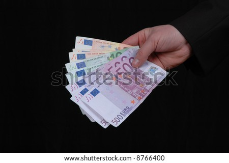 Euro in a mans hand isolated on black background - stock photo