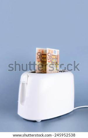 euro in the toaster over gray background - stock photo