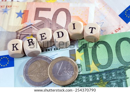 Euro Money and wood dice with the german word credit / Credit - stock photo